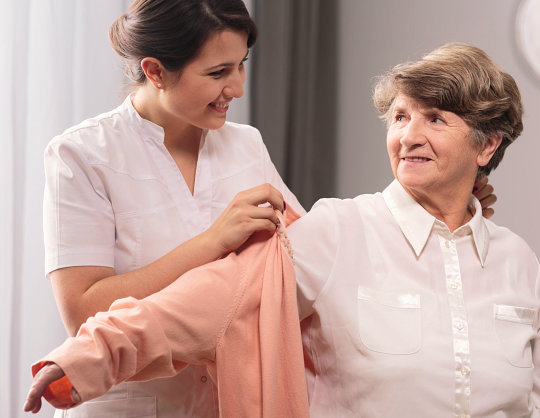 caregiver helps her patient in her clothes