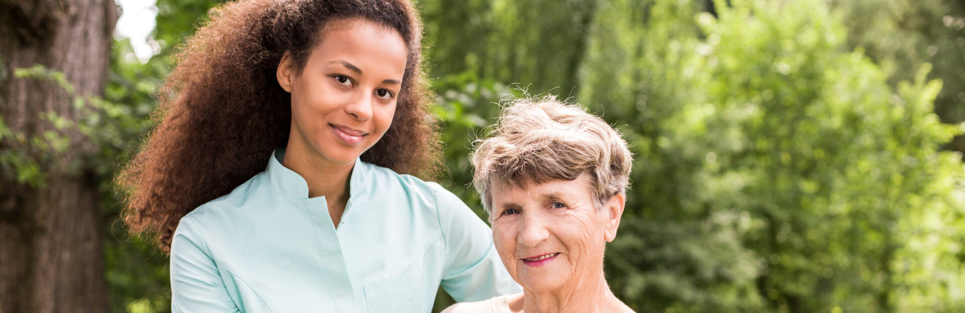 caregiver and her elderly patient smiling