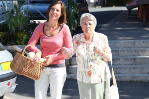 caregiver assisting elderly woman in shopping